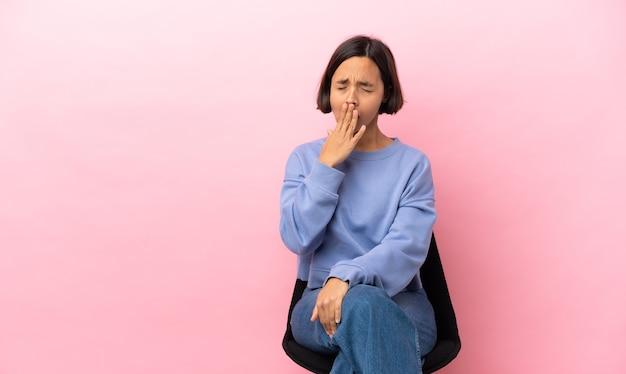 Jeune métisse femme assise sur une chaise isolée sur fond rose le bâillement et couvrant la bouche grande ouverte avec la main