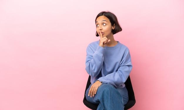 Jeune métisse femme assise sur une chaise isolée sur fond rose montrant un signe de silence geste mettant le doigt dans la bouche