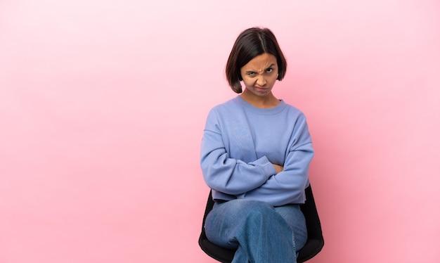 Jeune métisse femme assise sur une chaise isolée sur fond rose se sentir bouleversée
