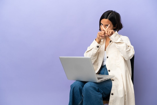 Jeune métisse femme assise sur une chaise avec ordinateur portable isolé sur fond violet faisant le geste d'arrêt avec sa main pour arrêter un acte