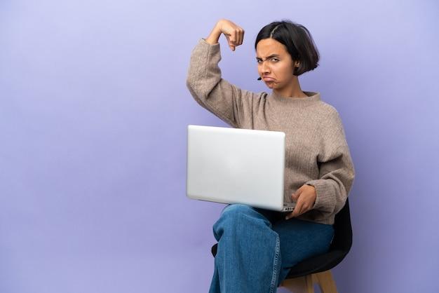 Jeune métisse femme assise sur une chaise avec ordinateur portable isolé sur fond violet faisant un geste fort