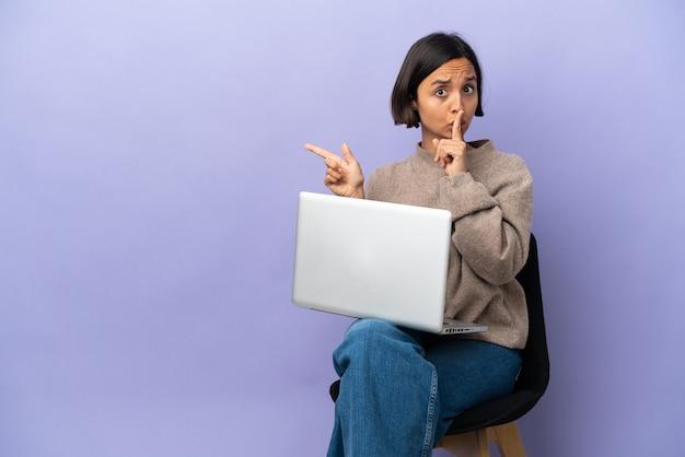 Jeune métisse femme assise sur une chaise avec ordinateur portable isolé sur fond violet pointant vers le côté et faisant le geste de silence
