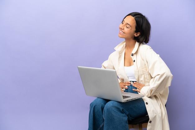 Jeune métisse femme assise sur une chaise avec ordinateur portable isolé sur fond violet posant avec les bras à la hanche et souriant