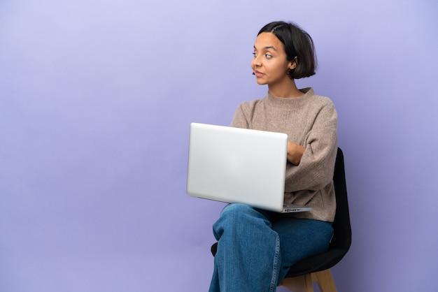 Jeune métisse femme assise sur une chaise avec ordinateur portable isolé sur fond violet en position latérale