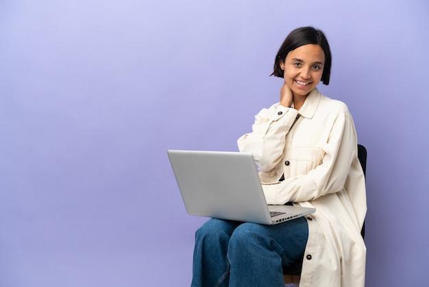 Jeune métisse femme assise sur une chaise avec ordinateur portable isolé sur fond violet en riant