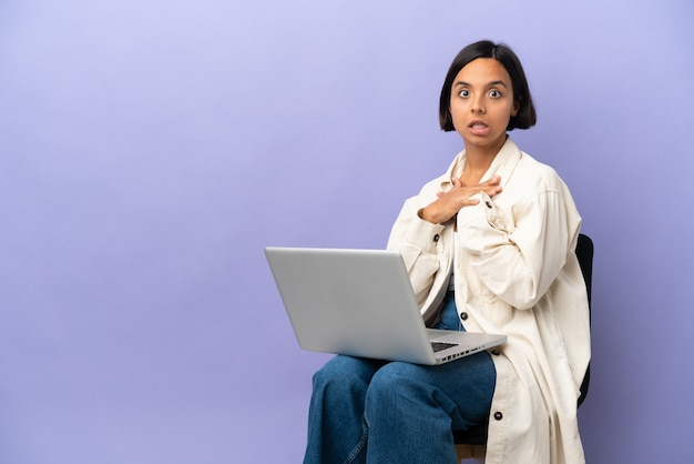 Jeune métisse femme assise sur une chaise avec ordinateur portable isolé sur fond violet surpris et choqué tout en regardant à droite