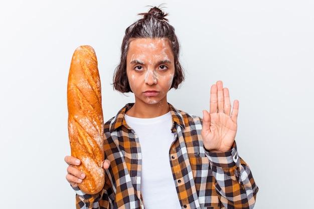 Jeune métisse femme faisant du pain isolé sur mur blanc debout avec la main tendue montrant le panneau d'arrêt, vous empêchant.