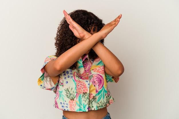 Jeune métisse femme isolée sur fond blanc gardant deux bras croisés, concept de déni.