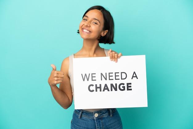 Jeune métisse femme isolée sur fond bleu tenant une pancarte avec du texte nous avons besoin d'un changement avec le pouce vers le haut