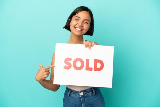 Jeune métisse femme isolée sur fond bleu tenant une pancarte avec texte vendu et en le pointant