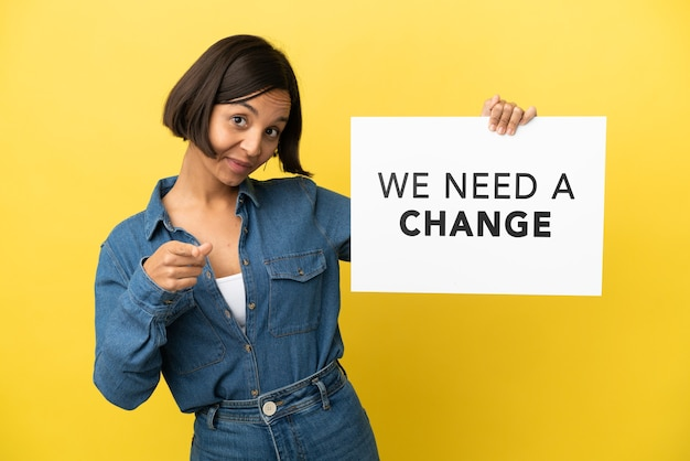Jeune métisse femme isolée sur fond jaune tenant une pancarte avec texte nous avons besoin d'un changement et pointant vers l'avant