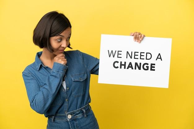 Jeune métisse femme isolée sur fond jaune tenant une pancarte avec texte nous avons besoin d'un changement et de la réflexion