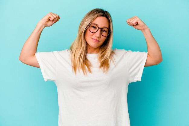 Jeune métisse femme isolée sur mur bleu montrant le geste de force avec les bras, symbole du pouvoir féminin