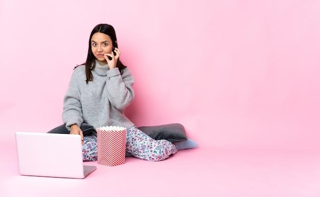 Jeune métisse femme mangeant du pop-corn tout en regardant un film sur l'ordinateur portable montrant un signe de geste de silence