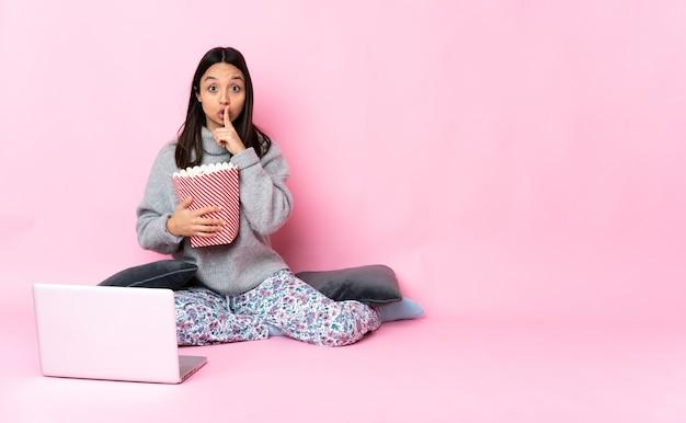 Jeune métisse femme mangeant du pop-corn tout en regardant un film sur l'ordinateur portable pointant vers le côté et faisant le geste de silence
