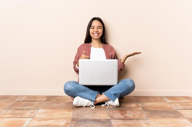 Jeune métisse femme avec un ordinateur portable assis sur le sol tenant copyspace imaginaire sur la paume pour insérer une annonce et avec les pouces vers le haut