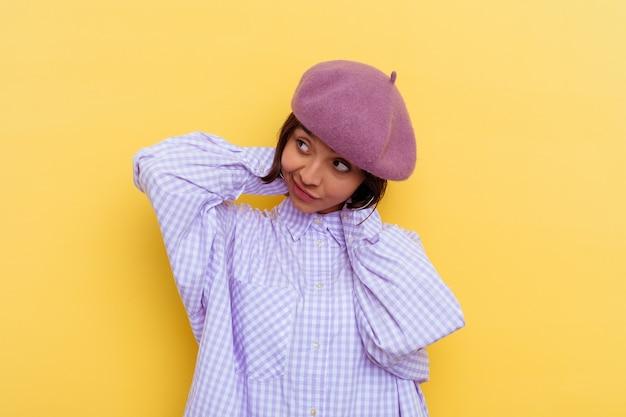 Jeune métisse femme portant un béret isolé sur fond jaune qui s'étend des bras, position détendue.