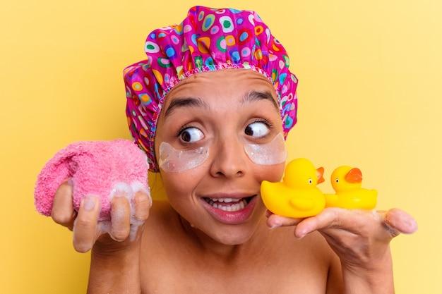 Jeune métisse femme prenant un bain tenant une éponge et des canards en caoutchouc