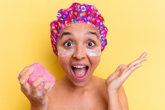 Jeune métisse femme prenant un bain tenant une éponge avec un patch sous les yeux