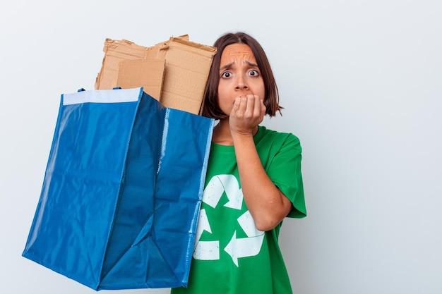 Jeune métisse femme recyclage carton isolé sur mur blanc se ronger les ongles, nerveux et très anxieux.