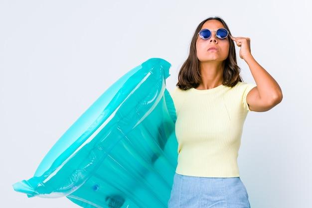 Jeune métisse femme tenant un matelas pneumatique concentré sur une tâche, gardant l'index pointant la tête.