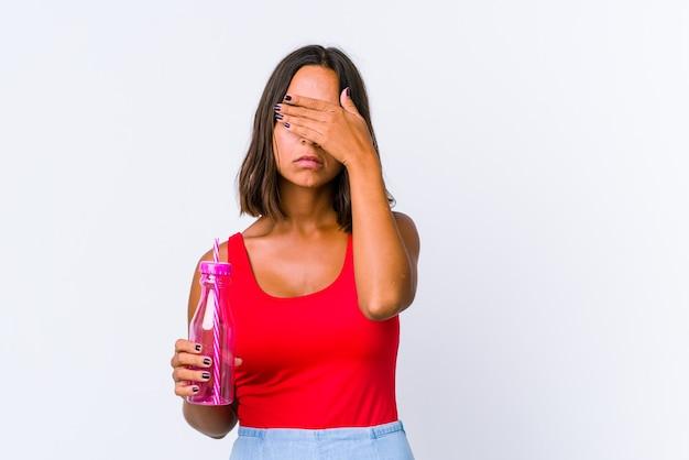 Jeune métisse femme tenant un milk-shake isolé peur couvrant les yeux avec les mains.