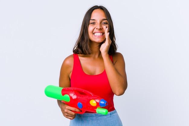 Jeune métisse femme tenant un pistolet à eau isolé disant un potin, pointant vers le côté rapportant quelque chose.