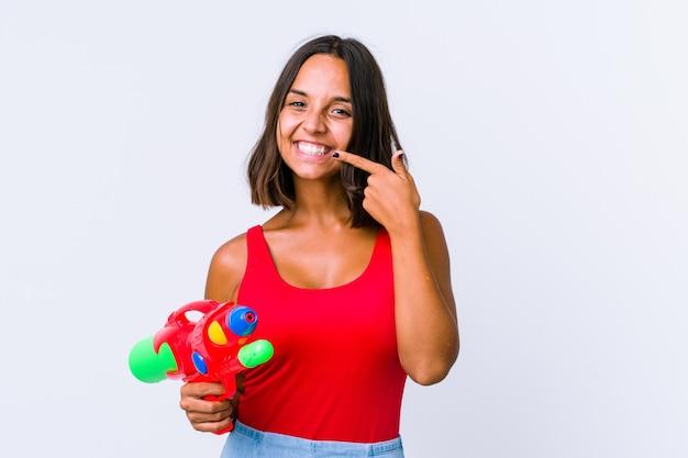 Jeune métisse femme tenant un pistolet à eau sourires isolés, pointant du doigt la bouche.
