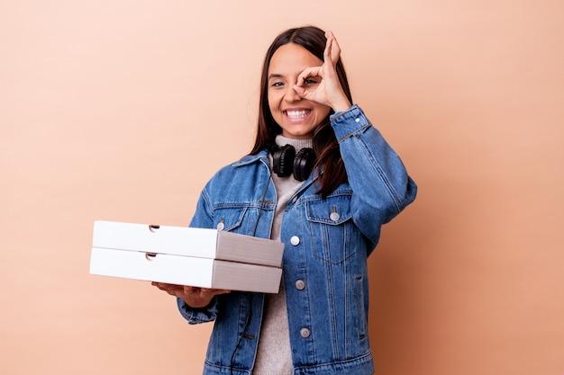 Jeune métisse femme tenant une pizza isolé excité en gardant le geste ok sur les yeux.