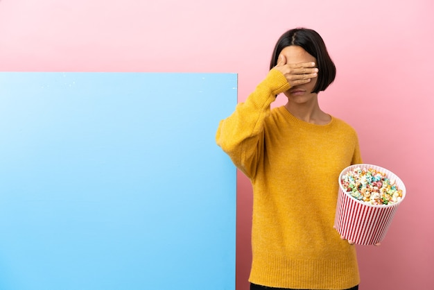 Jeune métisse femme tenant des pop-corn avec une grande bannière sur fond isolé couvrant les yeux par les mains. je ne veux pas voir quelque chose