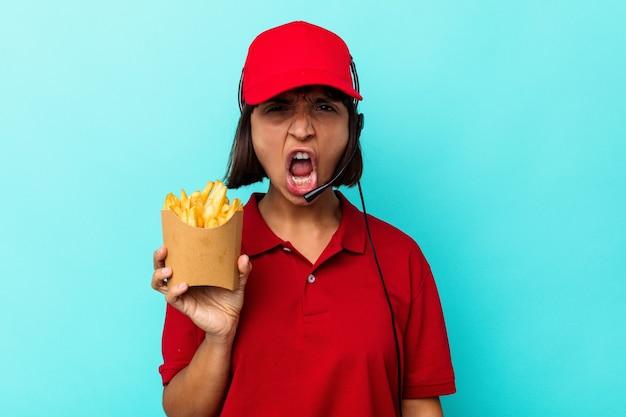Jeune métisse femme travailleur de restauration rapide tenant des frites isolées sur fond bleu criant très en colère et agressive.