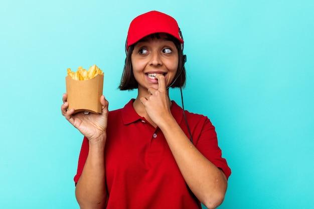 Jeune métisse femme travailleur de restauration rapide tenant des frites isolées sur fond bleu détendue en pensant à quelque chose en regardant un espace de copie.