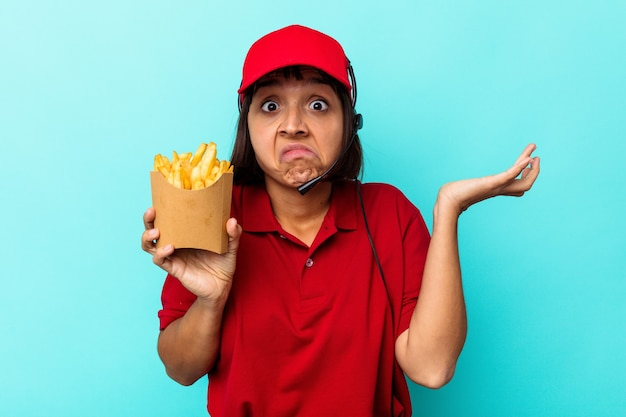 Jeune métisse femme travailleur de restauration rapide tenant des frites isolées sur fond bleu hausse les épaules et ouvre les yeux confus.