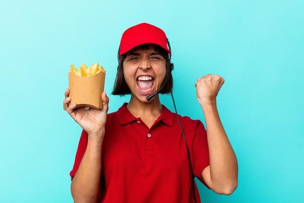 Jeune métisse femme travailleur de restauration rapide tenant des frites isolées sur fond bleu levant le poing après une victoire, concept gagnant.