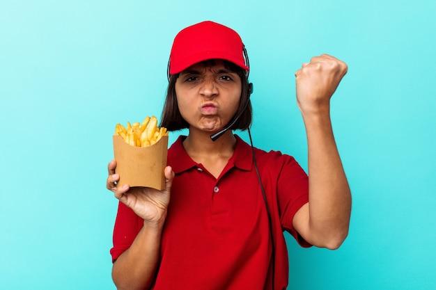 Jeune métisse femme travailleur de restauration rapide tenant des frites isolées sur fond bleu montrant le poing à la caméra, expression faciale agressive.
