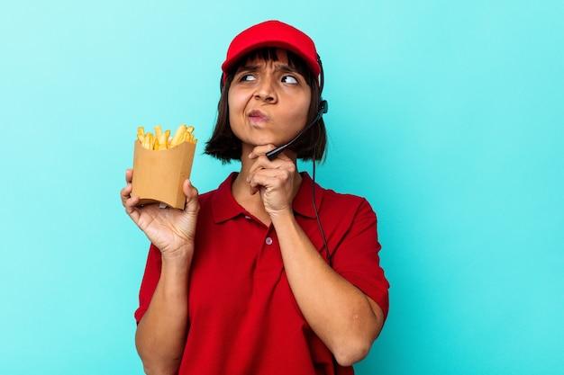 Jeune métisse femme travailleur de restauration rapide tenant des frites isolées sur fond bleu regardant de côté avec une expression douteuse et sceptique.