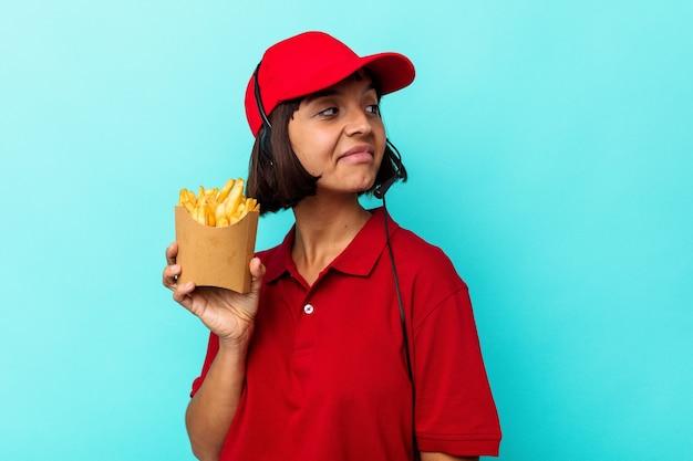 Jeune métisse femme travailleur de restauration rapide tenant des frites isolées sur fond bleu regarde de côté souriant, joyeux et agréable.