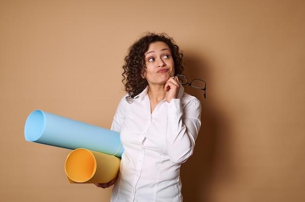Jeune métisse frisée femme tenant des rouleaux avec du papier design coloré et mettant son autre main sur son menton, regardant de côté sur un mur beige avec un regard pensif. copier l'espace