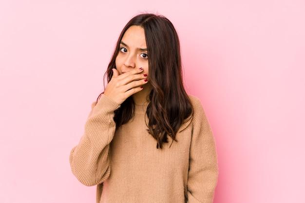 Jeune métisse hispanique femme isolée couvrant la bouche avec les mains à la recherche de peur.