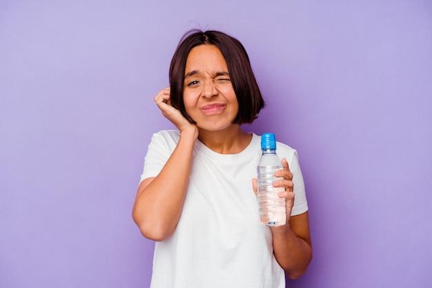 Jeune métisse tenant une bouteille d'eau isolée sur fond violet couvrant les oreilles avec les mains.