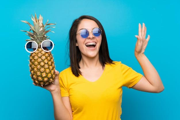 Jeune, mexicain, femme, isolé, bleu, tenue, ananas, lunettes soleil