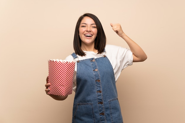 Jeune, mexicain, femme, isolé, mur, tenue, bol, pop-corn