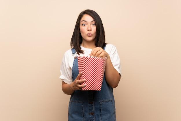 Jeune, mexicain, femme, mur isolé, manger, pop-corn