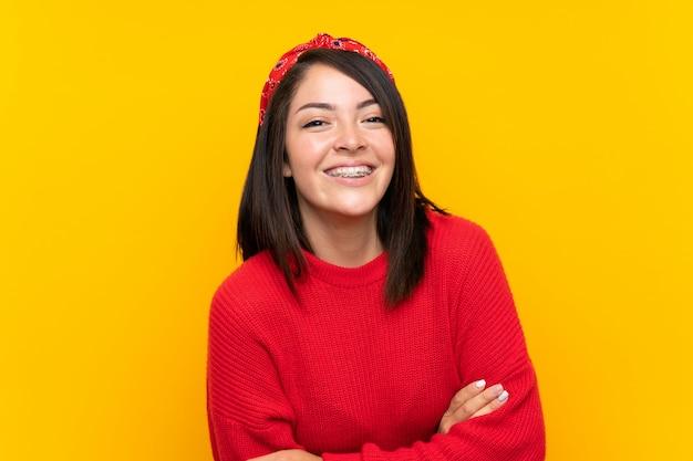 Jeune mexicaine avec un pull rouge sur un mur jaune en riant