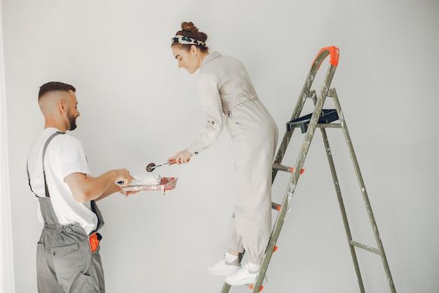 Le jeune et mignon couple répare la pièce