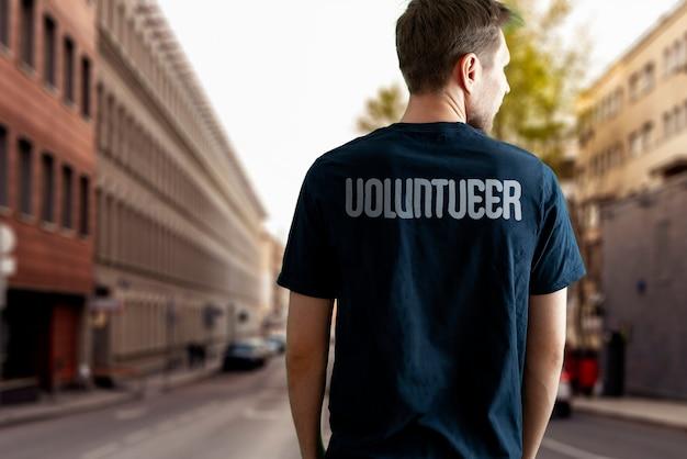 Un jeune militant bénévole masculin travaillant à l'extérieur, l'altruisme et le concept de travail d'équipe
