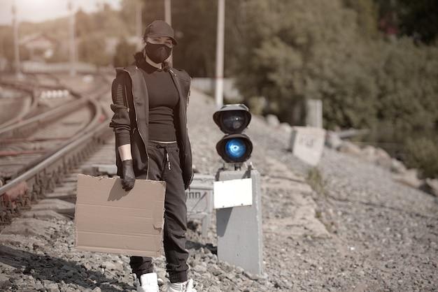 Une jeune militante avec une affiche à la main dans une gare, vêtue de vêtements noirs