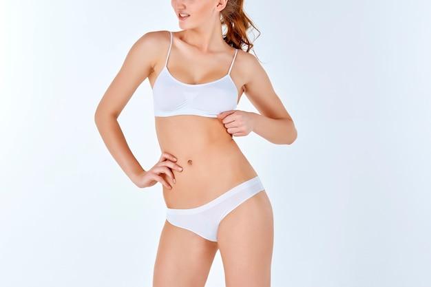 Jeune, mince, saine et belle femme en lingerie blanche