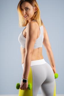 Jeune modèle féminin caucasien de fit sportif sur fond gris