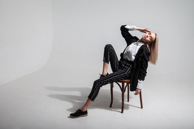 Jeune modèle féminin complet du corps dans des vêtements décontractés à la mode, touchant la tête et se penchant en arrière tout en étant assis sur une chaise sur fond gris